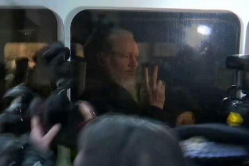 Assange giơ tay chữ V với phóng viên trước khi vào tòa ở London, Anh hôm nay. Ảnh: AFP.
