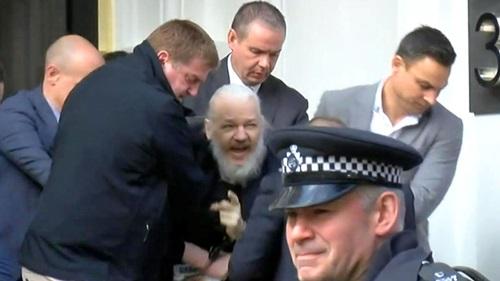 Cảnh sát Anh áp giải ông chủ WikiLeaks Julian Assange (tóc trắng) ra khỏi đại sứ quán Ecuador ở London hôm nay. Ảnh: Sky.