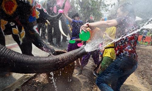 Voi và người dân vui đùa trong lễ hội té nước Songkran - lễ hội đánh dấu năm mới ở Thái Lan, tại thành phố Ayutthaya, cách Bangkok khoảng 80 km về phía bắc, hôm 11/4. Ảnh: Reuters.