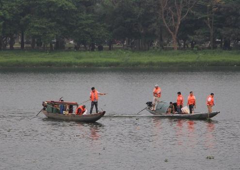 Nhân viên công ty du lịch giăng lưới ngang để vớt rác. Ảnh: Võ Thạnh