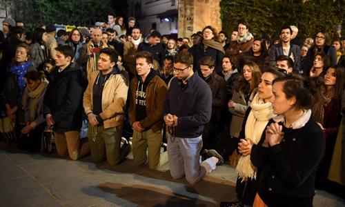 Người dân quỳ xuống cầu nguyện gần Nhà thờ Đức Bà Paris tối 15/4. Ảnh: AFP.