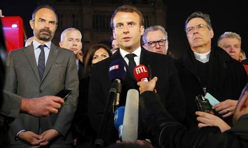 Tổng thống Pháp Emmanuel Macron hứa sẽ xây dựng lại Nhà thờ Đức Bà Paris khi tới thăm h iện trường. Ảnh: The Local.