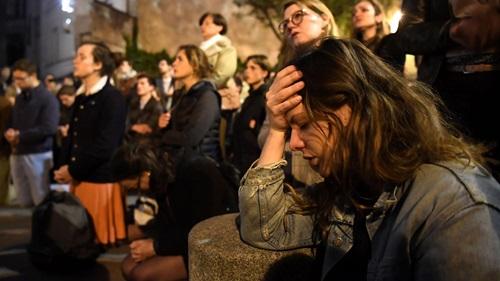 Một cô gái trẻ ôm đầu tiếc nuối, trong khi những người xung quanh quỳ xuống đường cầu nguyện khi chứng kiến đám cháy Nhà thờ Đức Bà Paris tối 15/4. Ảnh: Reuters.