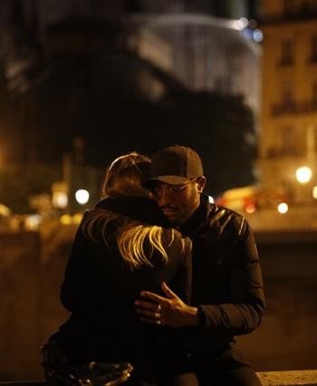 Hai người an ủi nhau tại hiện trường vụ hỏa hoạn Nhà thờ Đức Bà tối 15/4. Ảnh: AFP.