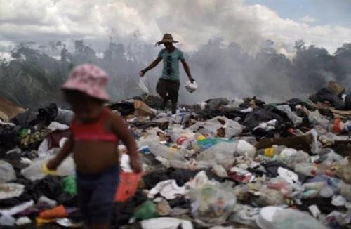Antony Calzazilla cùng con gái ở bãi rác Pacaraima hôm 13/4. Ảnh: Reuters.