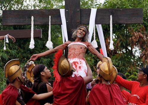 Một tín đồ Công giáo được đỡ xuống sau khi đóng đinh vào thánh giá gỗ trong lễ Thứ sáu Tuần thánh ở thành phố San Fernando, tỉnh Pampanga, hôm 19/4. Ảnh: Reuters.