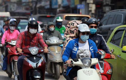 Người đi xe máy đeo khẩu trang tránh bụi trên đường Trường Chinh. Ảnh: Tất Định