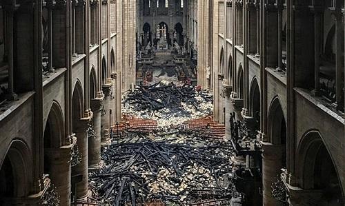 Mảnh vỡ rơi xuống từ mái vomnằm vương vãi khắp sàn nhà thờ Đức Bà sau vụ cháy. Ảnh: AFP.