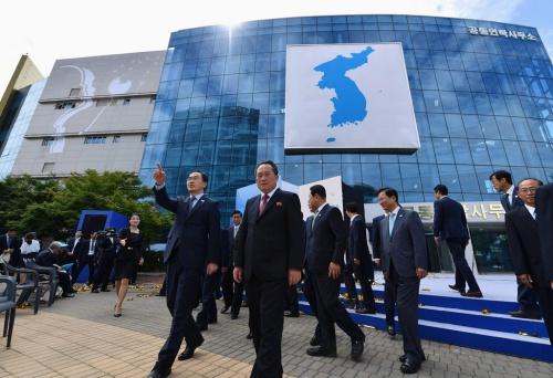 Các quan chức Triều Tiên và Hàn Quốc đứng trước Văn phòng liên lạc chung. Ảnh: NYT.
