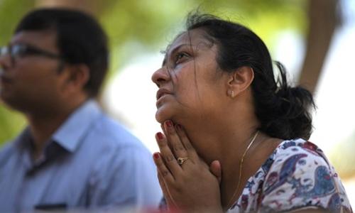 Một phụ nữ vừa khóc vừa cầu nguyện tại nhà thờ ThánhSebastian hôm nay. Ảnh: AFP.