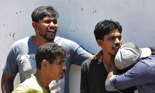 Thân nhân người bị nạn rơi nước mắt trong lúc chờ bên ngoài một nhà xác ở Colombo hôm 21/4. Ảnh: AP.