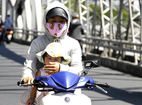 Người phụ nữ chở con gái qua cầu Trường Tiền (Huế) trưa ngày 20/4. Ảnh: Võ Thạnh.