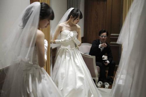 Kenzo Watanabe ngắm hôn thê Chiharu Yanagihara thử váy cưới hôm11/4. Ảnh: AP.