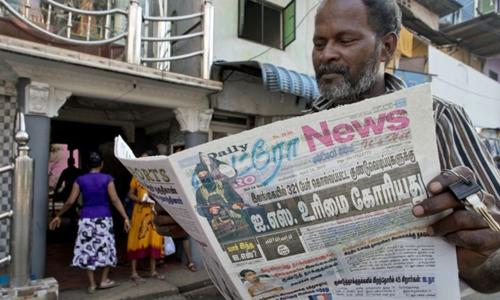 Một người dân Sri Lanka đọc báo ngày 23/4, trang nhất là thông tin IS nhận trách nhiệm vụ đánh bom liên hoàn. Ảnh: AP.