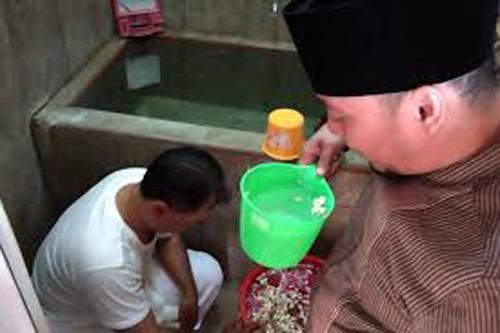 Giáo sĩ thực hiện nghi lễ tẩy trần cho ứng viênYayat tại trung tâm phục hồi. Ảnh: AFP.