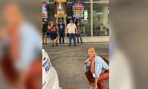 Shaymaa Ismaaeel ngồi xổm, cười tươi hết cỡ trước mặt những người biểu tình chống Hồi giáo. Ảnh: Twitter.