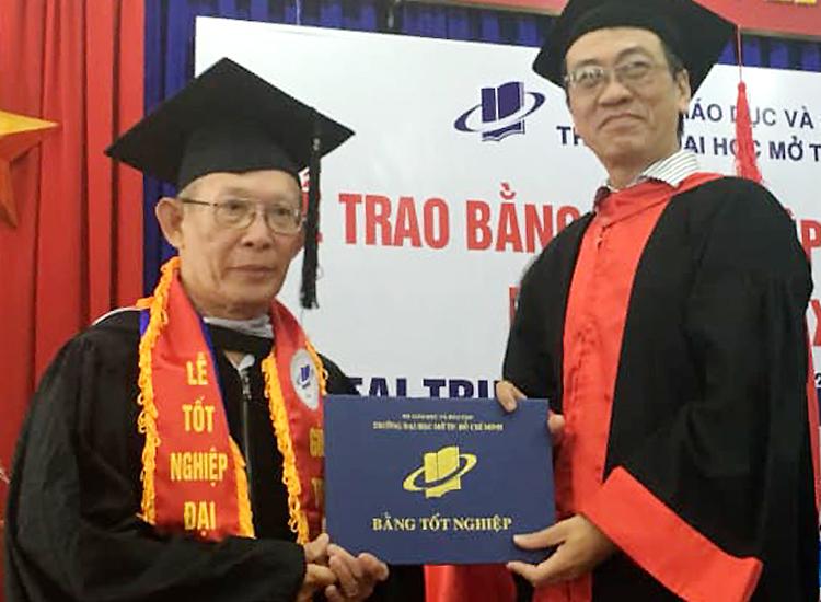 Ông Trần Xuân Thanh (trái) nhận bằng tốt nghiệp. Ảnh: Đại học Mở TP HCM.