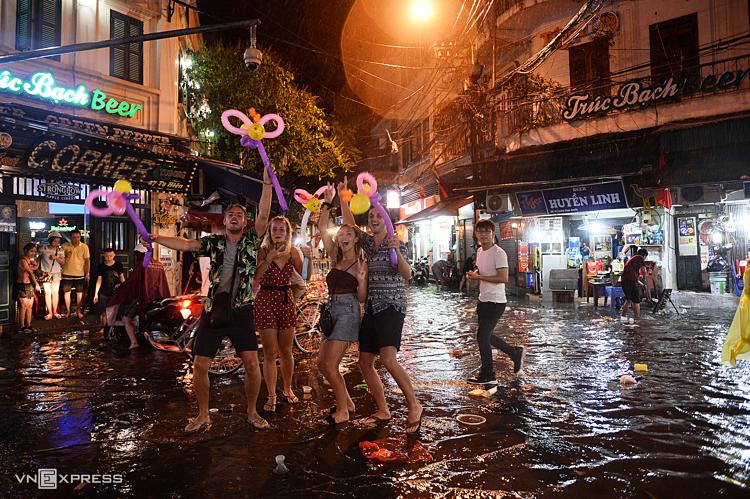 Nhóm khách nước ngoài pose hình trước khu phố cổ Tạ Hiện, tụ điểm chơi đêm này bịngập khoảng 30 cm khiến việc buôn bán phải tạm dừng. Ảnh: Giang Huy.