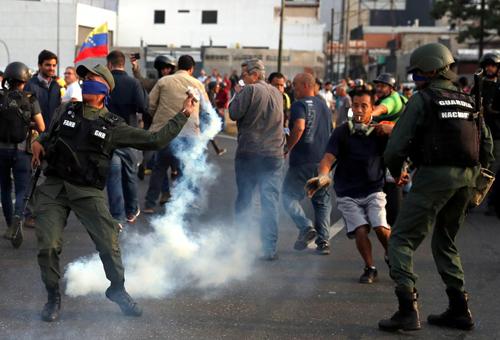 Một binh sĩ ném hơi cay gần căn cứ La Carlota ở thủ đô Caracas, Venezuela hôm nay. Ảnh: Reuters.