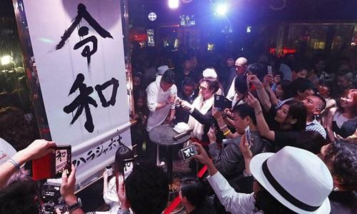 Người dân Nhật chụp tên triều đạiReiwa (Lệnh Hòa) trong sự kiện đếm ngược chào mừng tân Nhật hoàng và triều đại mới đêm 30/4 ở Tokyo. Ảnh: AP.