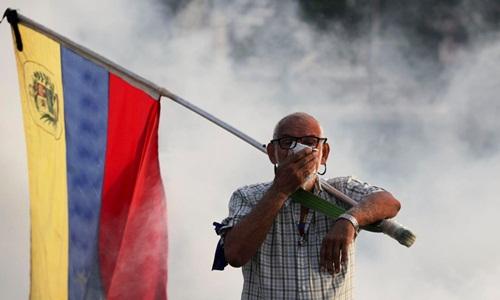 Một người phản đối chính quyền Maduro xuống đường biểu tình hôm 30/4. Ảnh: AP.