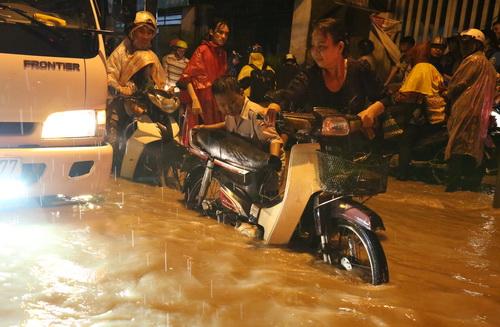 Nhiều người phải dắt bộ qua đoạn đường ngập ở phường Tân Hòa. Ảnh: Phước Tuấn