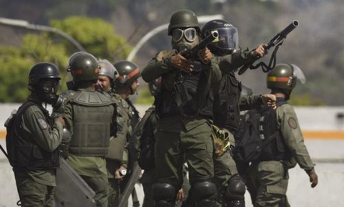 Lực lượng an ninh Venezuela bắn đạn cao su để giải tán người biểu tình hôm 1/5. Ảnh: AFP.