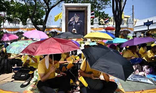 Dân Thái Lan mặc áo vàng, dùng ô che nắng tập trung bên đường để xem lễ rước kiệu của Quốc vương. Ảnh: AFP.