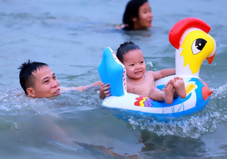 Dịp 1/5, miền Trung nắng nóng, nhiều người cho trẻ nhỏ ra biển giảm nhiệt. Ảnh: Nguyễn Đông