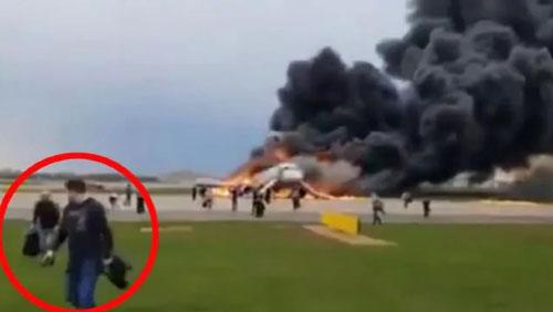 Hành khách trên chiếc Sukhoi Superjet 100 xách theo hành lý sơ tán khỏi máy bay hôm 5/5. Ảnh: News.com.au.