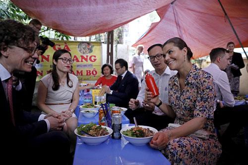 Công chúa Thụy Điển Victoria, váy hoa, và Đại sứ Thụy Điển tại Việt Nam Hogber, ngoài cùng bên trái, trao đổi về món bún bò. Ảnh: Giang Huy.