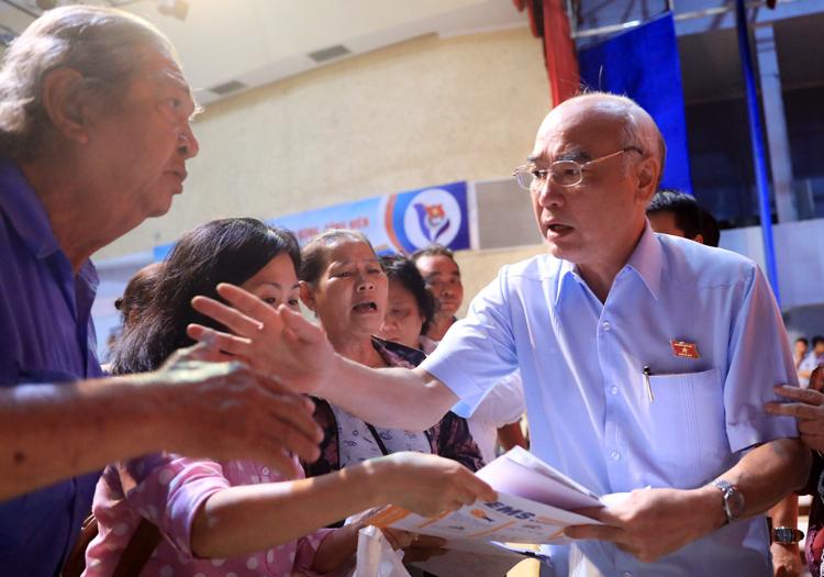 Ông Phan Nguyễn Như Khuê nhận hồ sơ, khiếu nại của người dân cuối buổi tiếp xúc cử tri. Ảnh: Hữu Khoa.