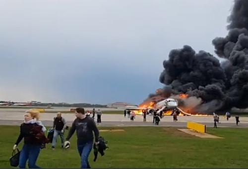 Một số hành khách cầm theo hành lý khi rời khỏi máy bay bốc cháy ngày 5/5. Ảnh chụp màn hình.