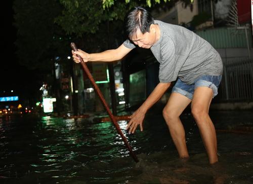 Người dân khu phố 1, phường Long Bình Tân khơi cống rảnh để nước thoát nhanh hơn trên quốc lộ 51. Ảnh: Phước Tuấn