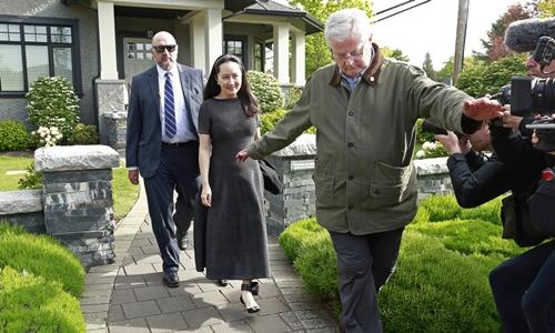 Mạnh Vãn Chu (giữa) ra khỏi nhà ở Vancouver ngày 8/5. Ảnh: AFP.
