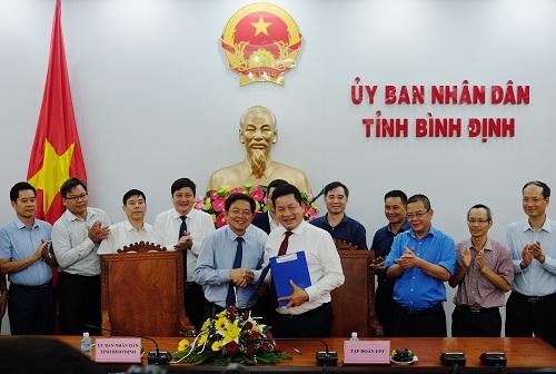 Chủ tịch UBND tỉnh Bình ĐịnhHồ Quốc Dũng (áo xanh) bắt tay Chủ tịch Hội đồng Quản trị FPT Trương Gia Bình.