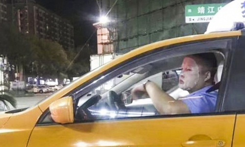 Bức ảnh tài xế Chen Yiqun vừa đắp mặt nạ vừa lái xe taxi được lan truyền rộng rãi trên mạng Trung Quốc hồi năm 2018. Ảnh: SCMP.