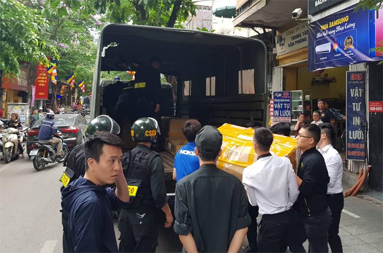 12h15, nhiều thùng các tông được cảnh sát đưa từ cửa hànglên xe tải chở đi. Ảnh: Tất Định