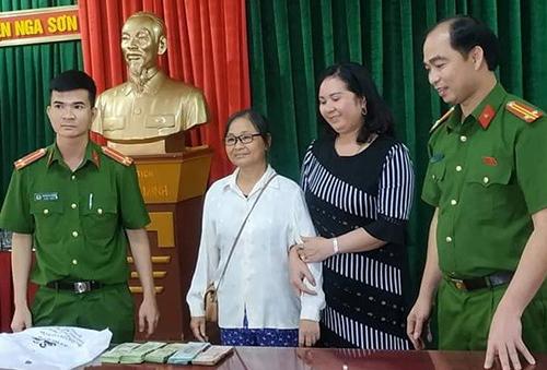 Công an trao trả số tiền cho bà Hoa. Ảnh: Lam Sơn.