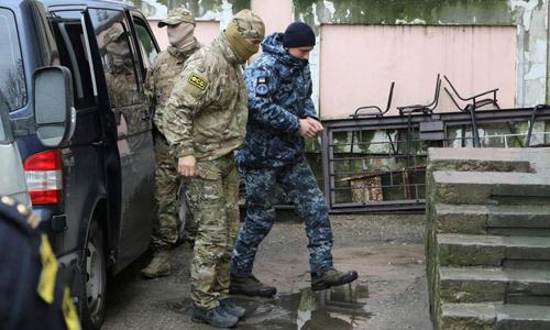 Một thủy thủ Ukraine (phải) bị áp giải tới tòa án thành phố Simferopol, Crimea, Nga hồi tháng 1. Ảnh: Reuters.