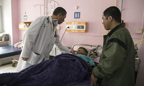 Thủ tướng Tshering hỏi thăm sức khỏe của một bệnh nhân tại bệnh viện quốc gia Jigme Dorji Wangchuck. Ảnh: AFP.