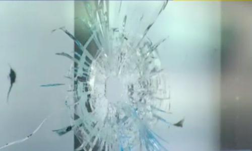 Vết đạn trên cửa kính quán cafe Việt, nơi xảy ra vụ nổ súng. Ảnh: NBC
