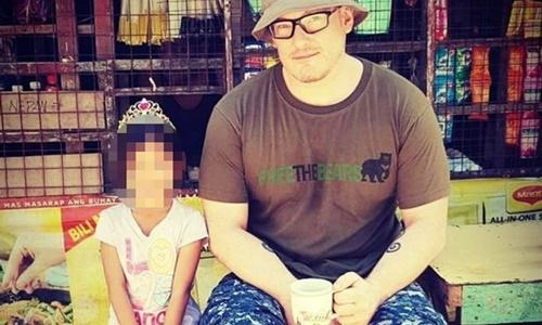 Trinnaman chụp ảnh cùng một bé gái Việt Nam. Ảnh: Mirror.