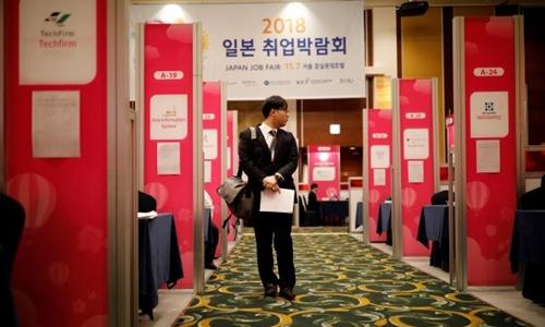 Một người tìm việc quan sát các gian giới thiệu việc làm trong Hội chợ Việc làm Nhật Bản 2018 tổ chức ở Seoul Hàn Quốc ngày 7/11/2018. Ảnh: Reuters.