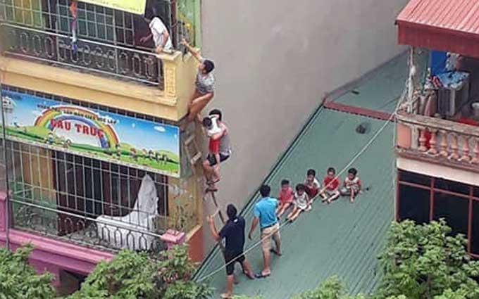 Các bé ở trường mầm non tư thục được giải cứu qua đường ban công tầng ba. Ảnh: Huyền Ngọc