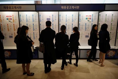 Người tìm việc đọc quảng cáo tuyển dụng trong Hội chợ Việc làm Nhật Bản 2018 ở Seoul, Hàn Quốc hôm 7/11/2018. Ảnh: Reuters.