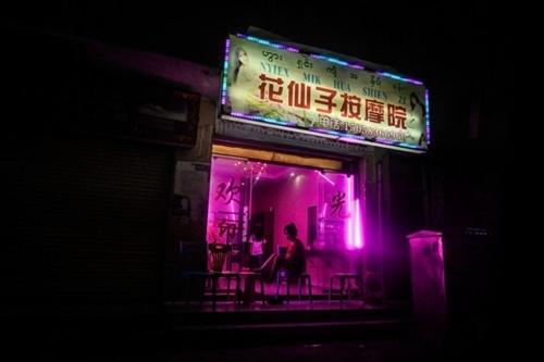 Đêm xuống, ánh đèn màu hồng hắt ra từ những tiệm mát xa kiêm nhà thổ chiếu sáng những con đường tối tăm ở Panghsang hôm 17/4. Ảnh: AFP.
