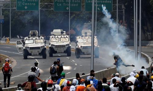 Quân đội Venezuela điều động xe bọc thép để giải tán người biểu tình ngày 30/4. Ảnh: Reuters.