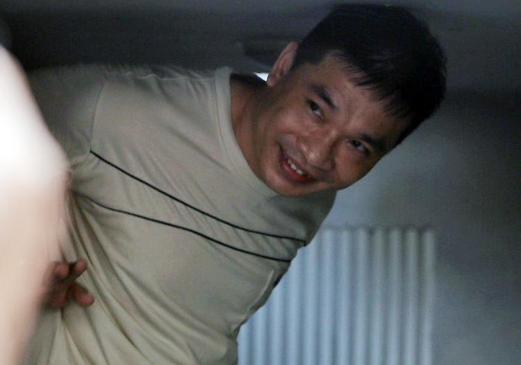 Ở trên xe tù, Văn Kính Dương cố nhoài người, vẫy tay với người thân. Ảnh: Thành Nguyễn.