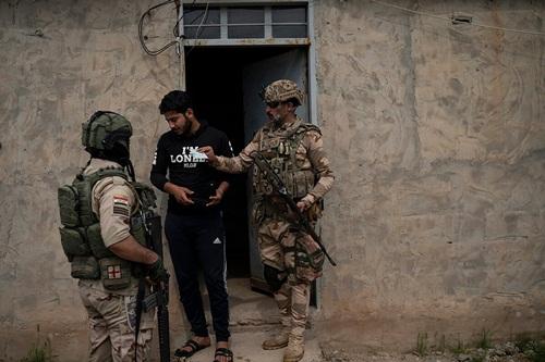 Binh sĩ thuộc Sư đoàn 20 của quân đội Iraq kiểm tra nhân thân của một người đàn ông ở Badoush hồi tháng 4. Ảnh: AP.